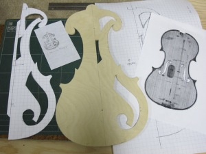 First steps in building the electric fiddle. The tiny sketch was my concept thumbnail drawing. I used the x-ray of a Stradivarius to create the design on graph paper. Then I enlarged my design to full size to make the half pattern. Carefully cut out, I used the full size design to make the plywood template. I only cut the holes in one half because I can flip the template over to make the other half. On some of the instruments I may leave the holes out entirely.