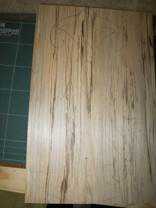 Run through the band saw and table saw, the board shows an attractive pattern. I traced the design onto it, using nails to permanently mark the center line.