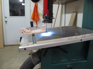 I built a jig to hold the neck square, then I tilted the band saw table to cut the angle of the foot. Then I used a fine-toothed saw to trim the sides, followed by carving with chisels.