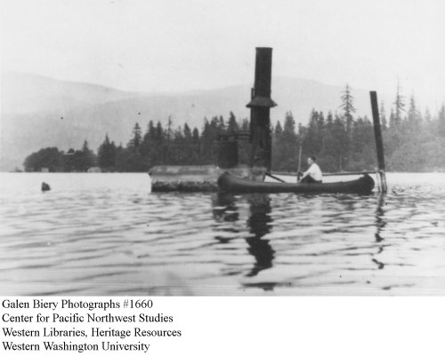 A canoeist paddles past the wreckage of a steamer tentatively identified as the Cora Blake. Photograph courtesy of the Center for Pacific Northwest Studies (WWU), Biery Collection. Used by permission.
